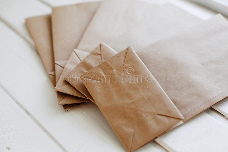 Ecologic craft package. Paper bags on light wooden floor. Simple brown paper bags for lunch or meal. The layout for the design. Environmental ship packages stock photography