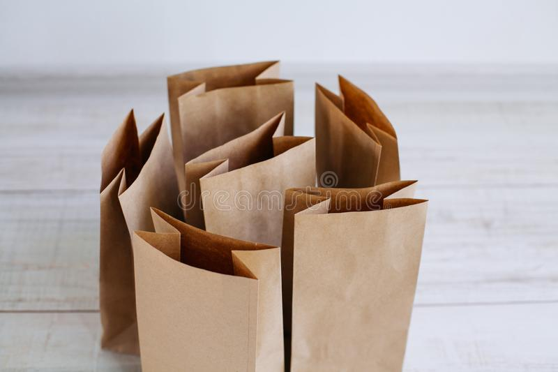Ecologic craft package. Paper bags on light wooden floor. Simple brown paper bags for lunch or meal. The layout for the design. Environmental ship packages stock images