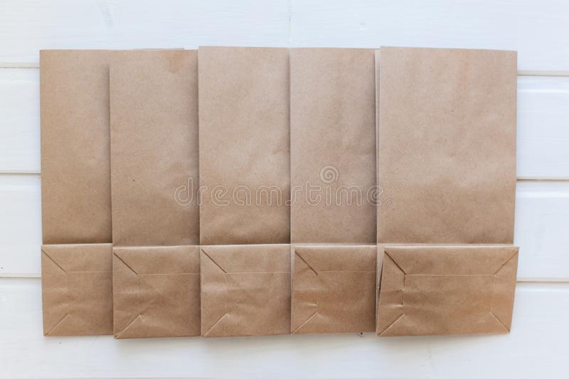 Ecologic craft package. Paper bags on light wooden floor. Simple brown paper bags for lunch or meal. The layout for the design. Environmental ship packages royalty free stock photo