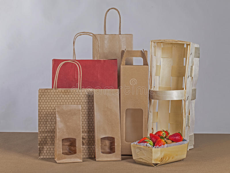 Paper bags and wooden basket. With strawberies stock images