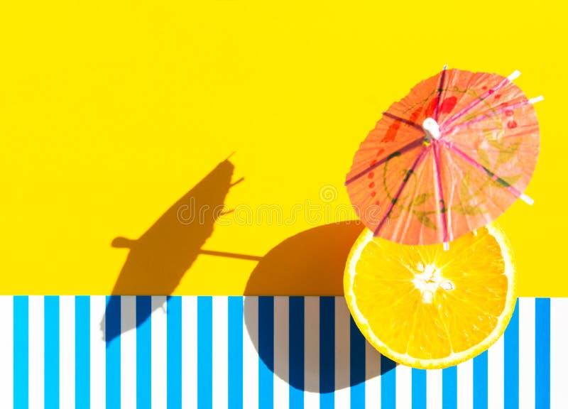 Paper beverage umbrella fresh juicy orange on bright yellow blue and white striped background. Harsh light hard shadow. Trendy stock photos