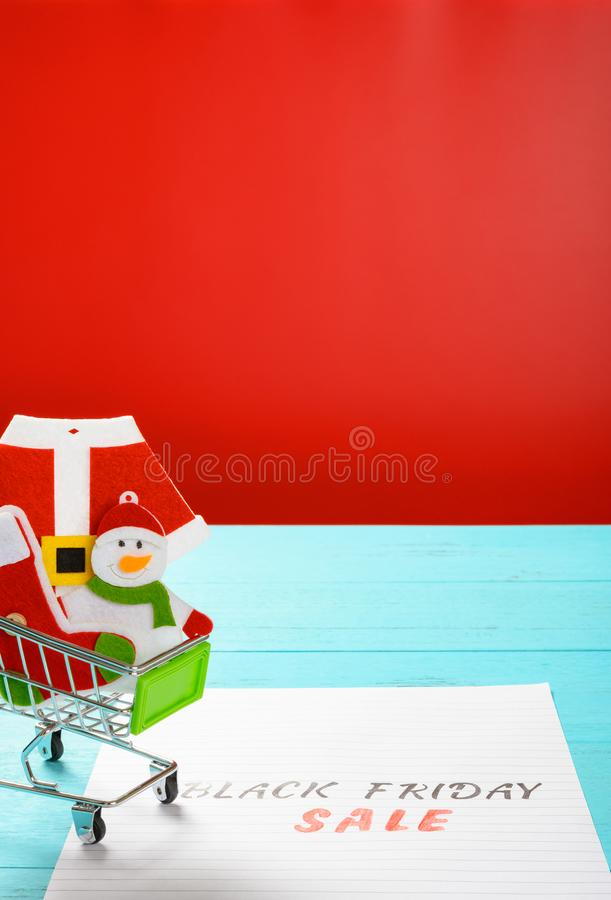 Paper with black friday sale with a shopping cart with Christmas decoration vertical composition royalty free stock photo