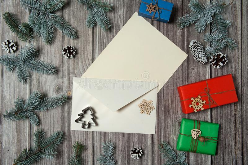 Paper blank, envelope, gift boxes, fir branches, cones, wooden decorative toys, snowflakes on a wooden background. Christmas, win royalty free stock image
