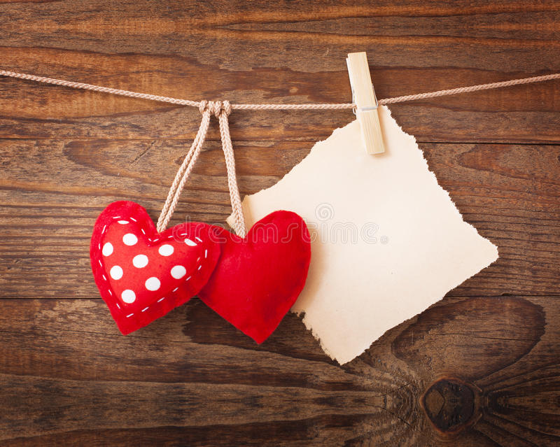 Paper blank and two red heart hanging on wooden background royalty free stock image