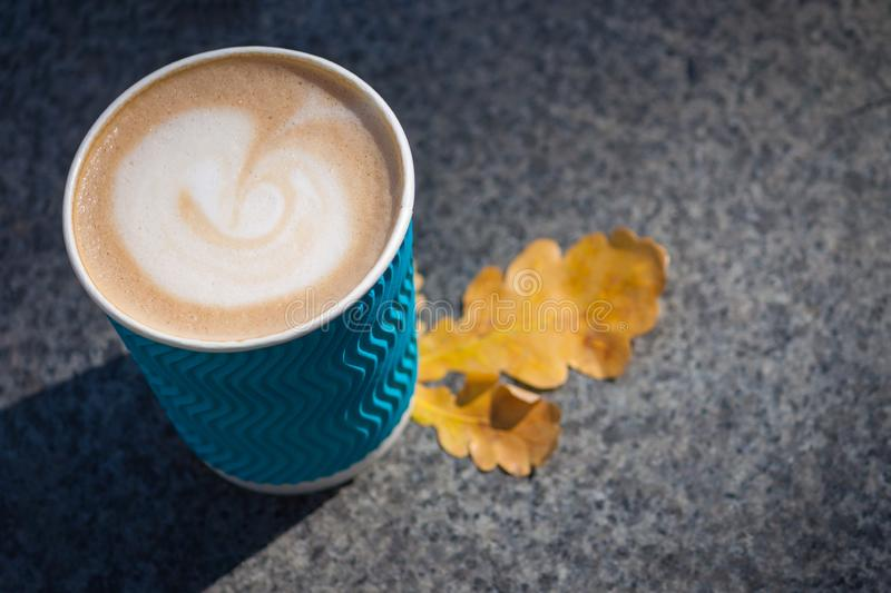 Paper blue coffee cup on the autumn fall leaves and stone grey background. Copy space. Close up stock photos