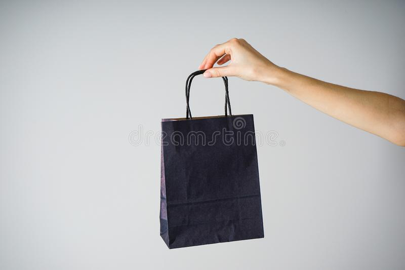 Paper blue craft bag, eco packaging in a female hand, on a gray background royalty free stock photo
