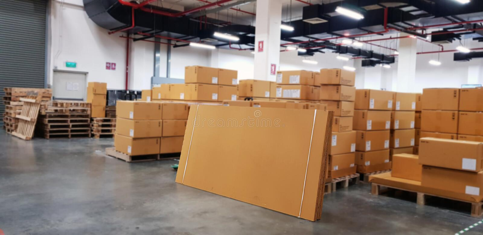 Paper board empty on blurred background. Perspective brown paper over blur in large warehouse logistic or distribution center,Can. Be used mock up for montage royalty free stock photos
