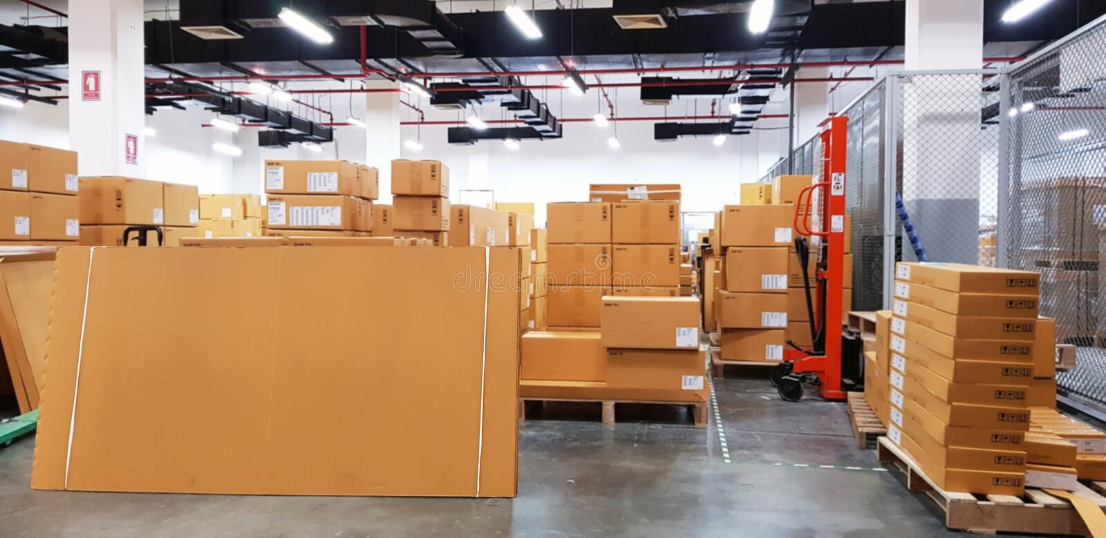 Paper board empty on blurred background. Perspective brown paper over blur in large warehouse logistic or distribution center,Can. Be used mock up for montage stock photos