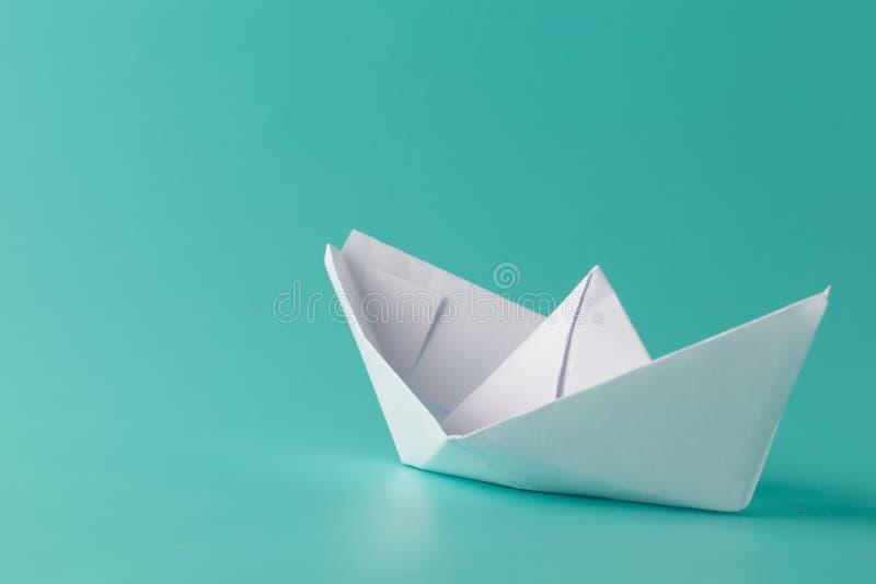 Paper boat on aquamarine background stock photos