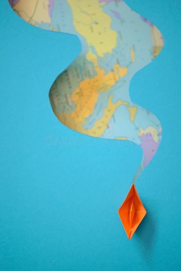 Paper boat making waves on a paper background map stock photography