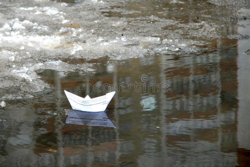 Paper boat in a puddle in early spring royalty free stock photo