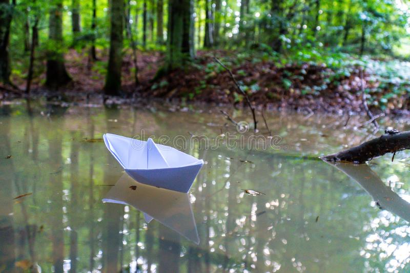 A paper boat sailing in the mountain forest lake. Small Paper Boat. Paper Ship Floating in the Sea. Origami Paper Boat Sailing. Mu stock images