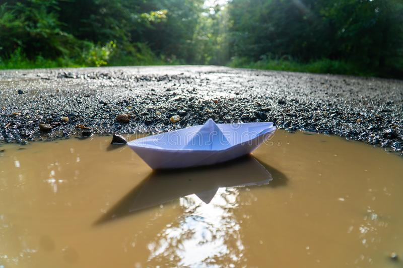A paper boat sailing in the mountain forest lake. Small Paper Boat. Paper Ship Floating in the Sea. Origami Paper Boat Sailing. Mu royalty free stock image