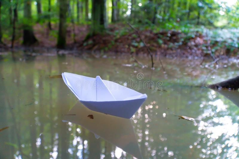 A paper boat sailing in the mountain forest lake. Small Paper Boat. Paper Ship Floating in the Sea. Origami Paper Boat Sailing. Mu stock image