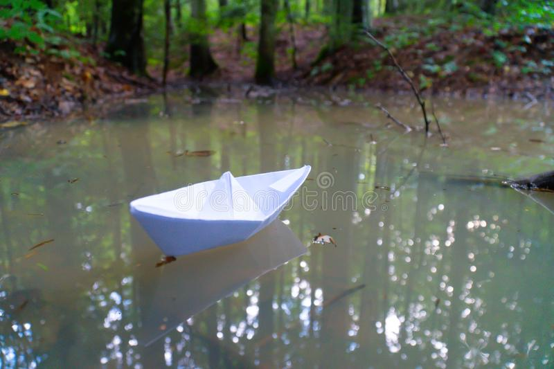A paper boat sailing in the mountain forest lake. Small Paper Boat. Paper Ship Floating in the Sea. Origami Paper Boat Sailing. Mu royalty free stock photo