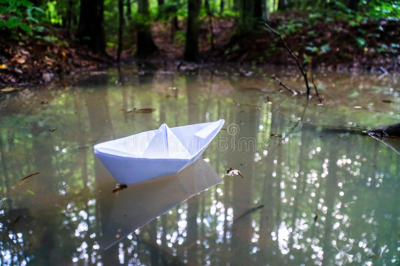 A paper boat sailing in the mountain forest lake. Small Paper Boat. Paper Ship Floating in the Sea. Origami Paper Boat Sailing. Mu stock photos