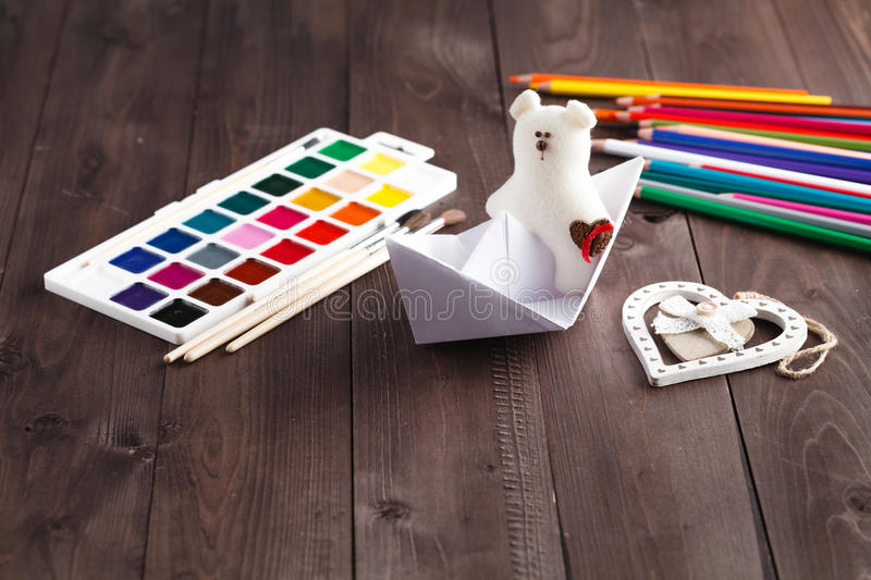 Paper boat and soft toy on wooden table stock photography