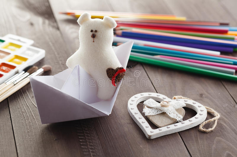 Paper boat and soft toy on wooden table royalty free stock photo