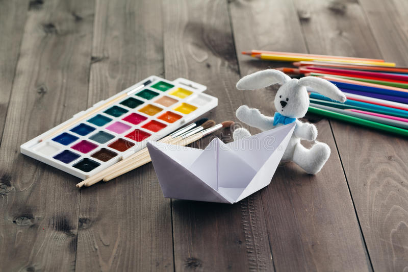 Paper boat and soft toy on wooden table royalty free stock image