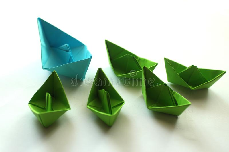 Origami paper ships in light blue and green colors. stock photos