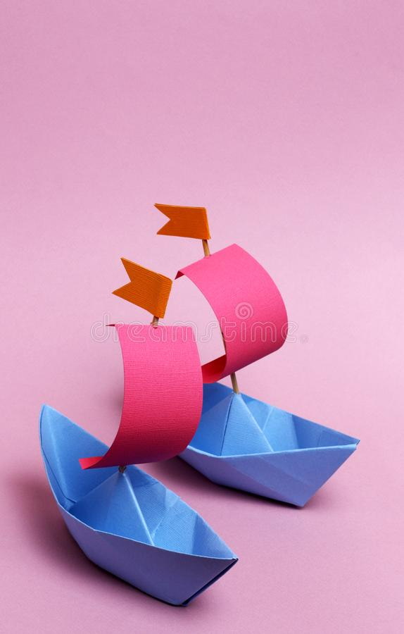 2 paper boats on a pink background stock photos