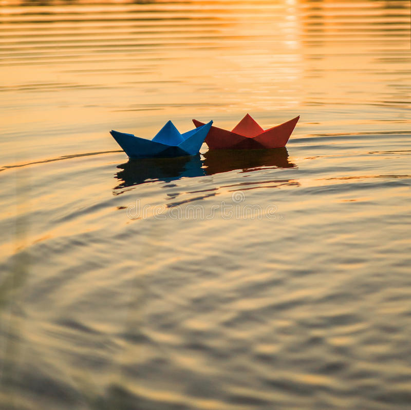Paper boats. Red and blue paper boats floating in the sunset royalty free stock photography