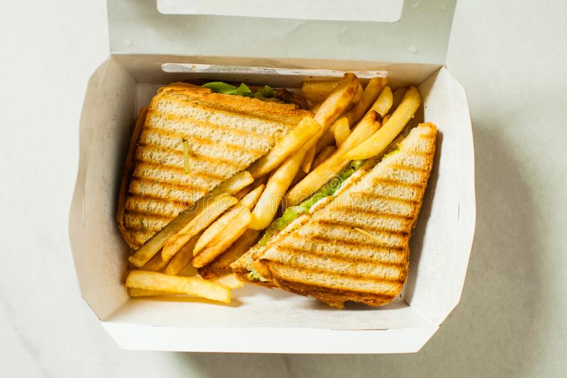Paper box with chicken sandwich with french fries. Top view stock photo