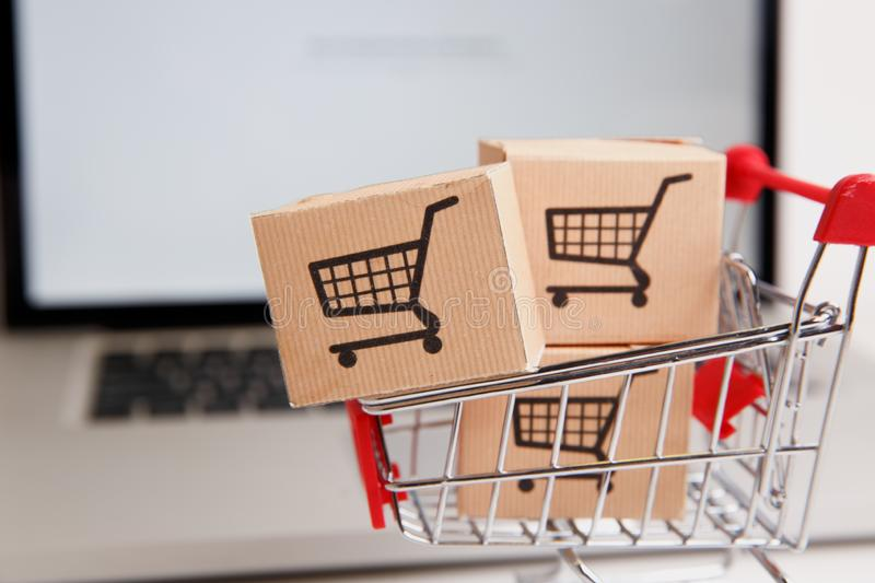 Many paper boxes in a small shopping cart on a laptop keyboard. Concepts about online shopping that consumers can buy. Paper boxes in a shopping cart on a laptop royalty free stock image