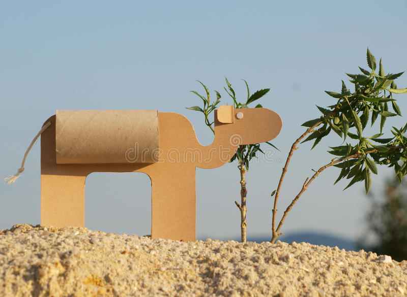 A paper camel. A child made paper camel from toilet paper tube and paperboard on the sand with a plants and blue sky stock photos