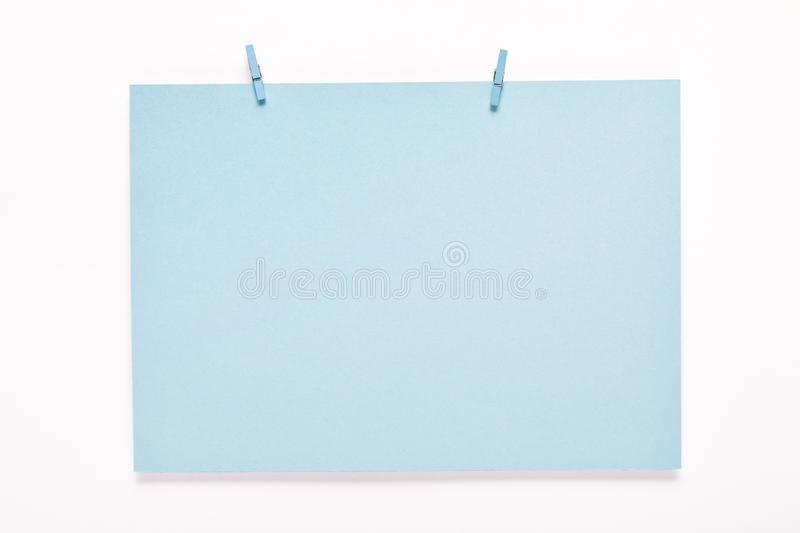 Paper card on clothes peg on white background. Blue paper card on a clothes peg on a white background stock image