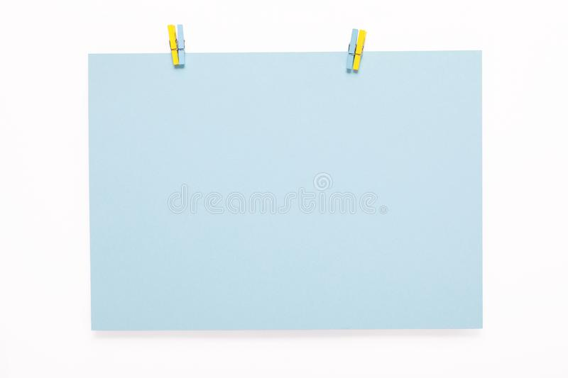 Paper card on clothes peg on white background stock images