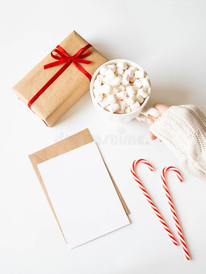 Paper card for letter, envelope, xmas decoration and female hand holds a white mug with hot drink and marshmallows on white stock photos