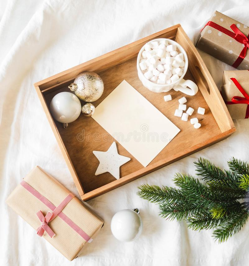 Paper card for letter in wood tray, mug with hot drink and marshmallows and xmas decoration. Flat lay for Merry Christmas or Happy royalty free stock photos