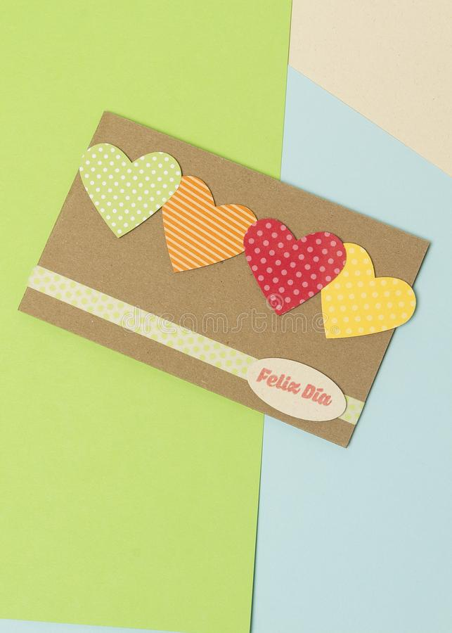 Paper card with hearts with happy day spanish phrase and blue and yellow green colors royalty free stock image