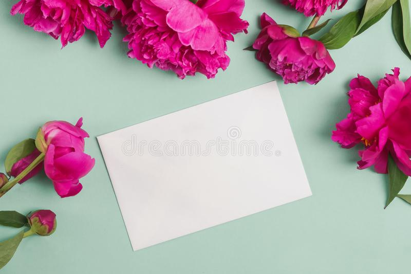 Paper card mock-up on the table with beautiful peonies. Paper card mock-up and pink beautiful peonies on pastel green or mint background, top view royalty free stock photography