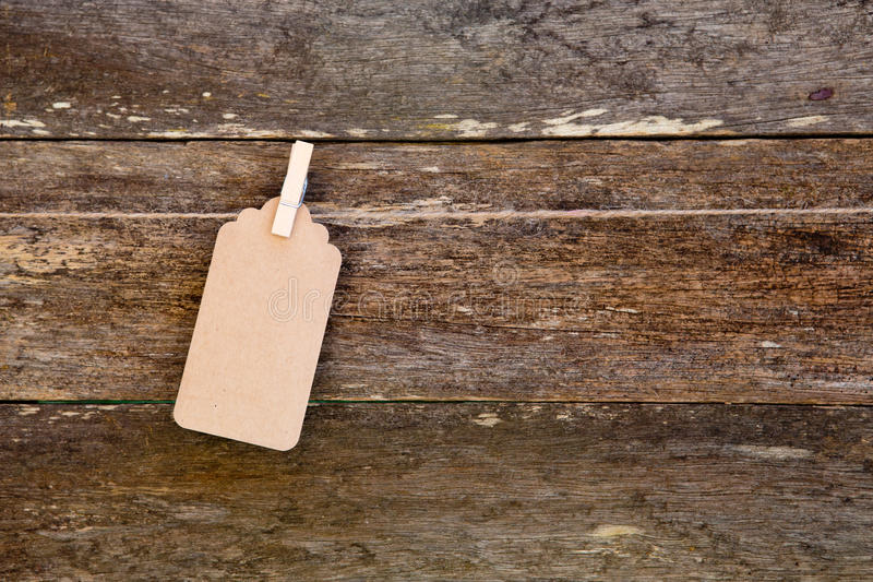 Paper - cardboard label hanging on clothespin against old wooden. Paper - cardboard label hanging on clothespin against rustic old wooden background royalty free stock photo