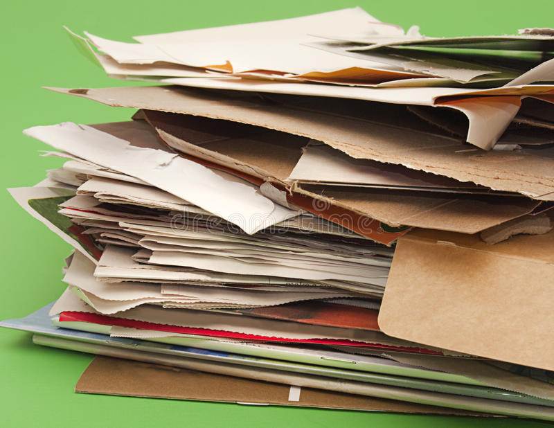 Paper and cardboard for recycling. Stack of paper and cardboard products piled up for recycling. Studio shot against green background to suggest environmental stock photography