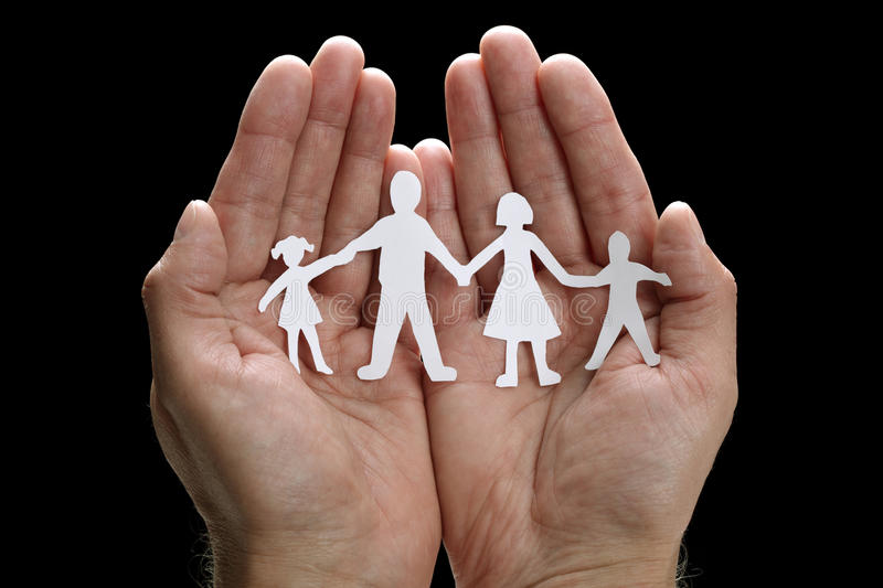 Paper chain family protected in cupped hands. Cutout paper chain family with the protection of cupped hands, concept for security and care stock image