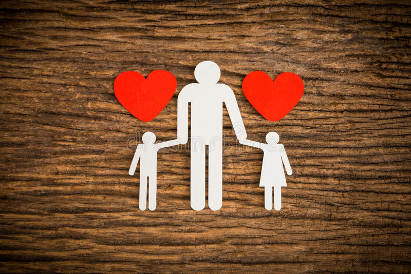 Paper chain family and red heart symbolizing. On wooden background. love family concept royalty free stock image