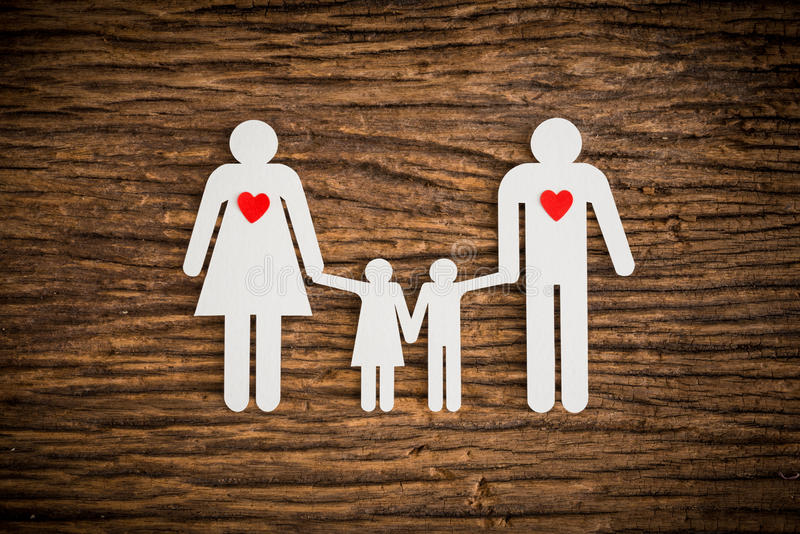 Paper chain family and red heart symbolizing. On wooden background. love family concept royalty free stock photos