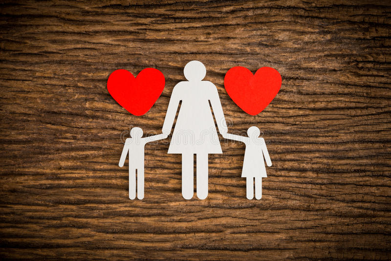 Paper chain family and red heart symbolizing. On wooden background. love family concept stock photography