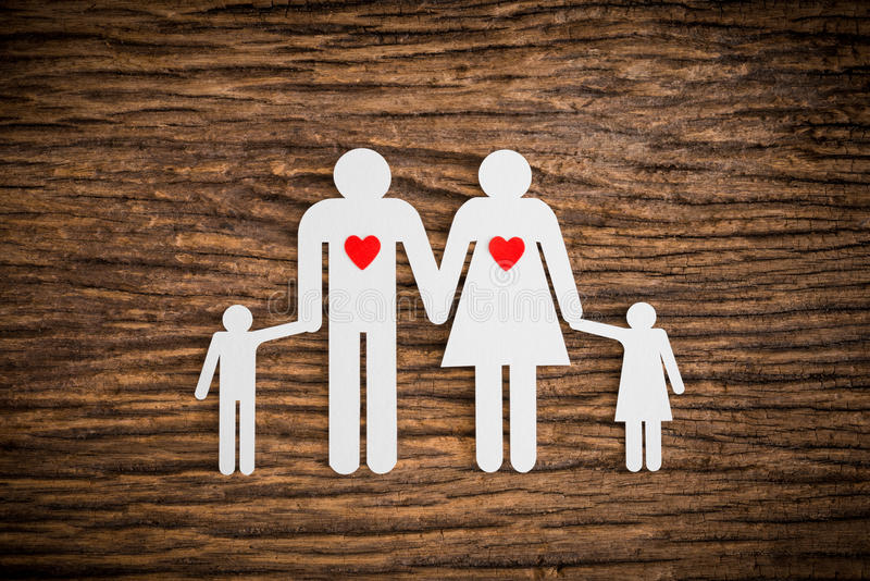 Paper chain family and red heart symbolizing. On wooden background. love family concept royalty free stock photography