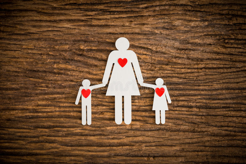 Paper chain family and red heart symbolizing. On wooden background. love family concept royalty free stock images