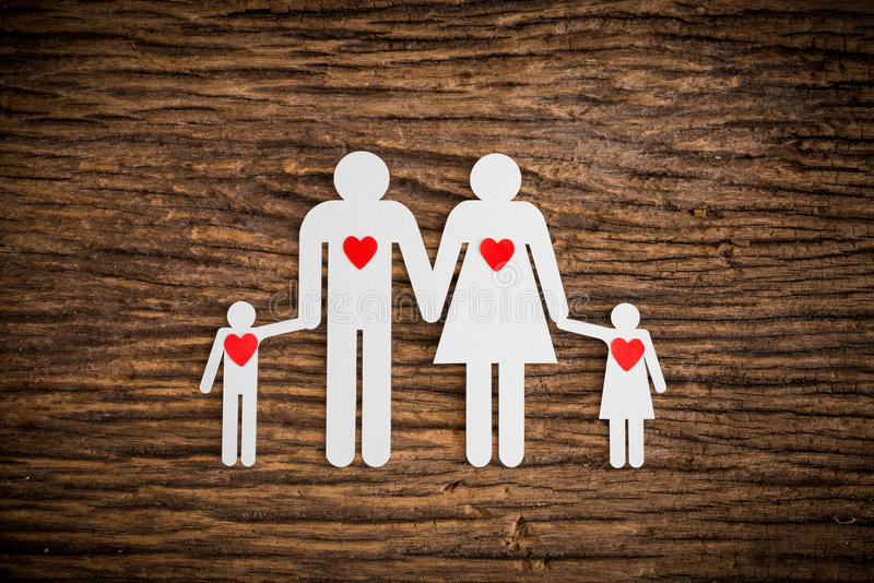 Paper chain family and red heart symbolizing. On wooden background. love family concept stock photos