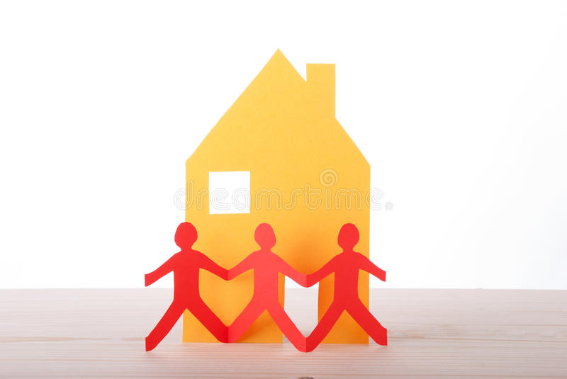 Paper Chain in Front of a House. Three Paper Chain People in front of a Yellow House stock photos