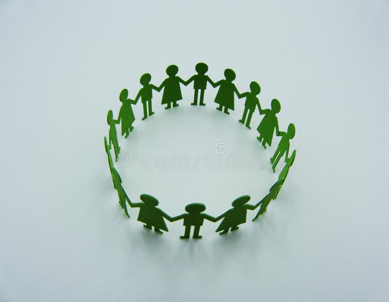 Paper children figurine make a circular dance on white background royalty free stock images