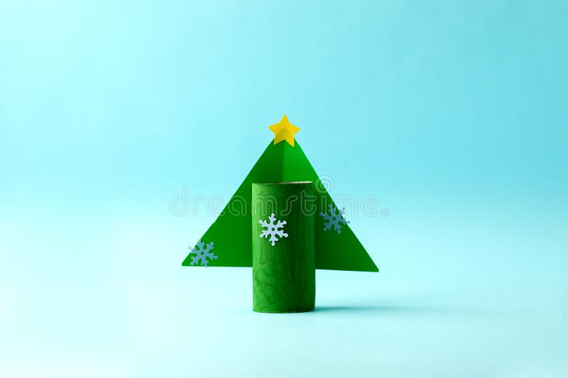 Paper Christmas tree for Happy new year Merry Christmas party. Easy craft for kids on blue background, simple diy idea from toilet. Rool tube, recycle concept stock photography