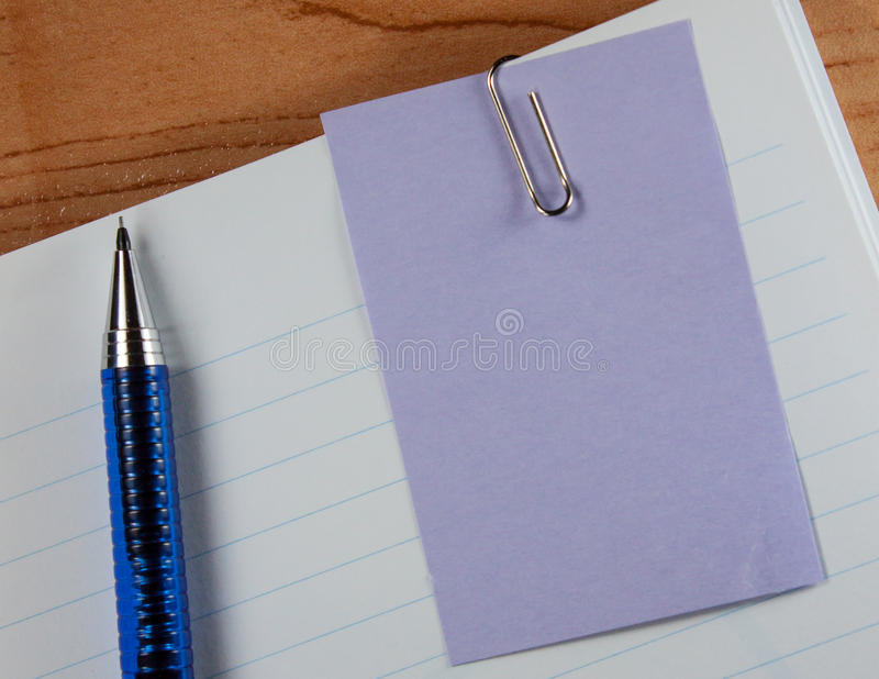 Paper clip and pencil. Clip on a piece of paper over a white note and pencil stock photos