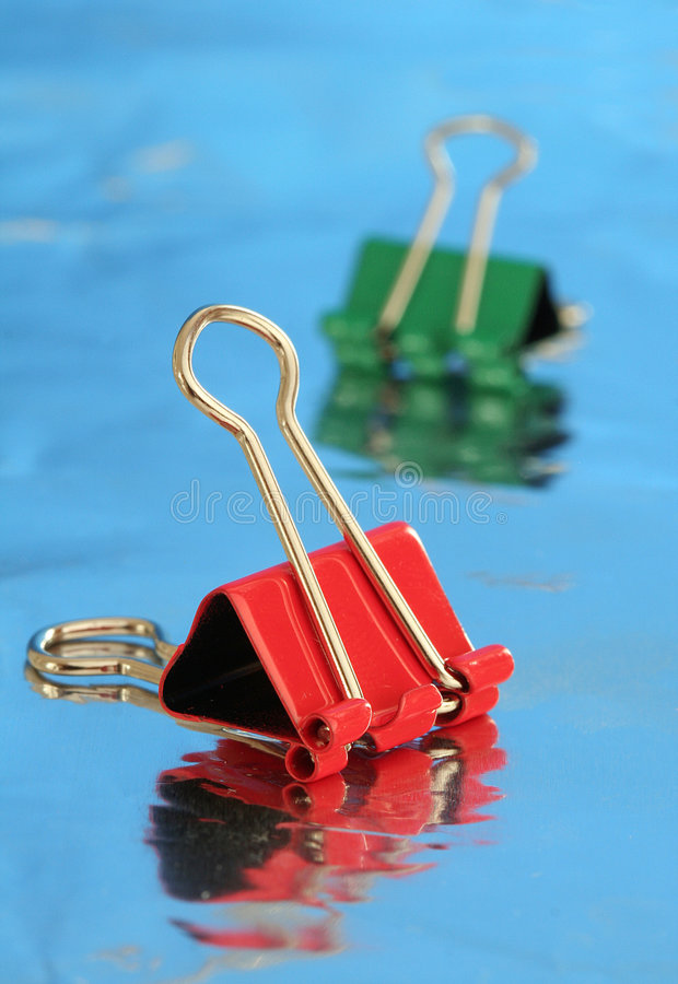 Paper clips. Two paper clips on a refletive surfaces, shallow DOF with front clip in focus royalty free stock photography