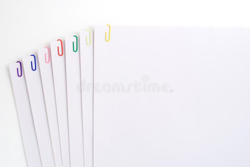 Paper clips. Fasten the white papers together with seven colors paper clips royalty free stock images